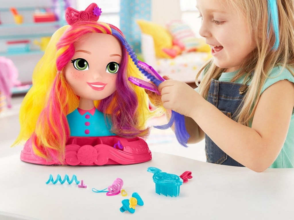 girl playing with doll hair styling head
