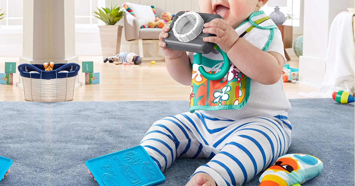 baby wearing a bib and using a toy camera