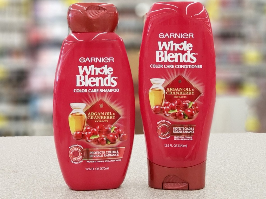 two red bottles of Garnier Whole Blends shampoo and conditioner on checkout counter at Walgreens