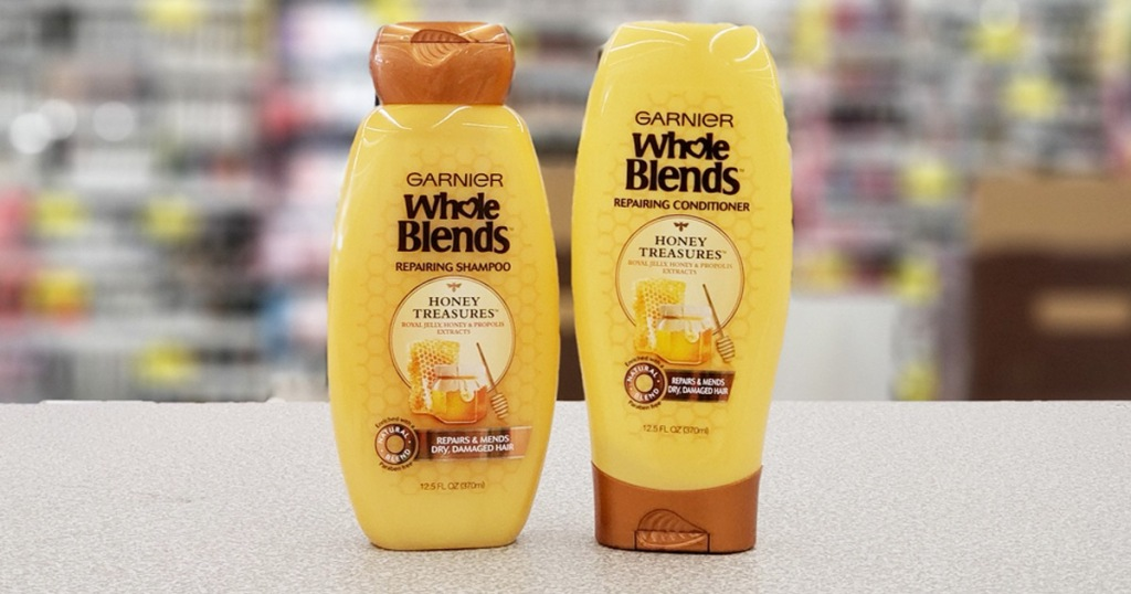 two yellow and brown bottles of Garnier Whole Blends shampoo and conditioner on checkout counter at Walgreens