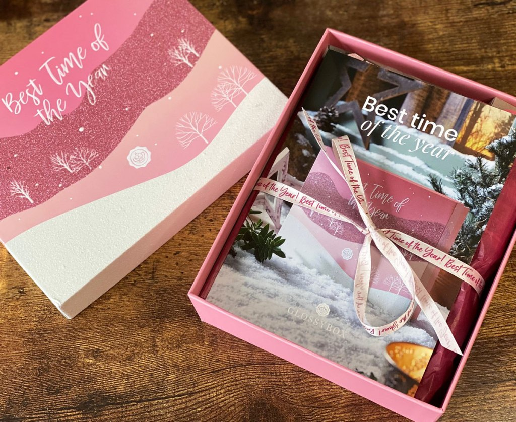 opened glossybox on wood table showing contents wrapped in a pink bow