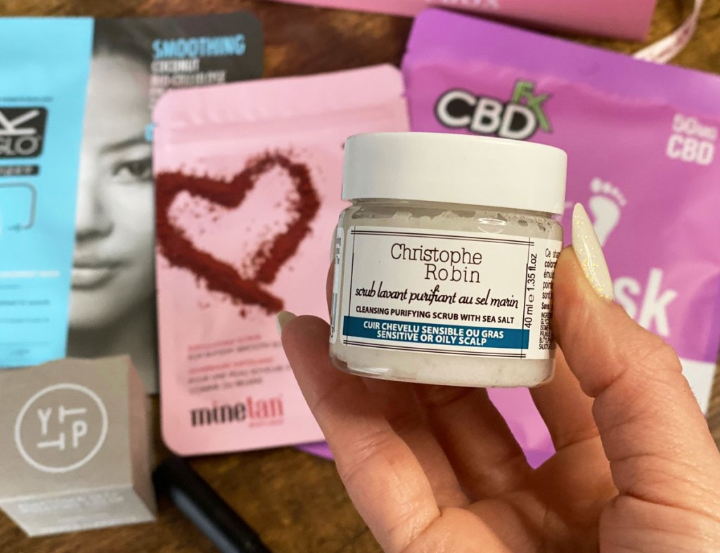 woman with white nails holding up a white jar of Christophe Robin salt scrub with other glossybox products in the background