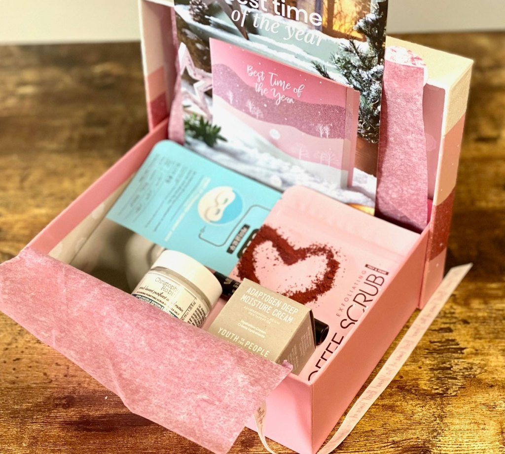 pink glossybox opened with pink tissue paper and various skincare and beauty products inside of it