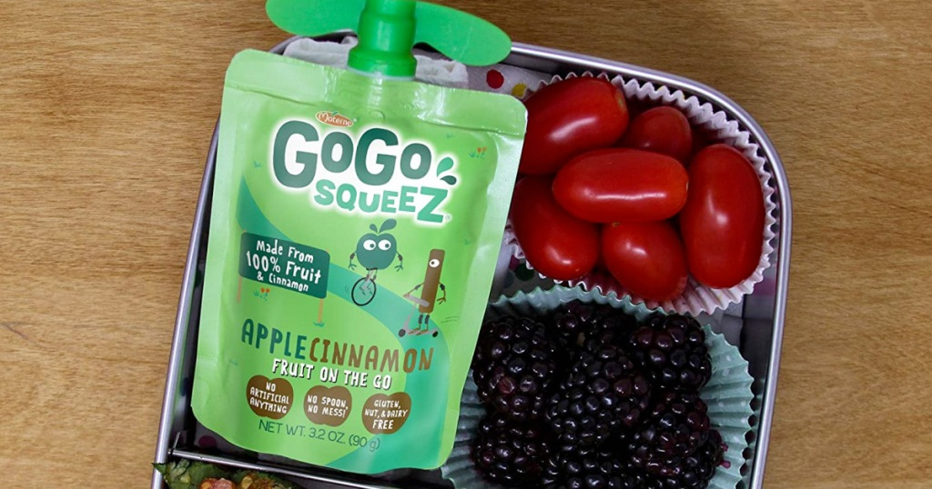 green go-go squeez applesauce packet on a metal lunchbox with blackberries and cherry tomatoes