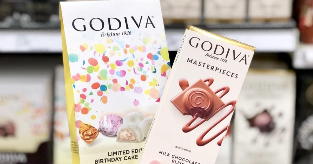 person holding up white bag of Godiva birthday cake chocolates and Godiva milk chocolate bar