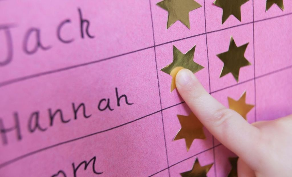 A finger placing a gold star on a chart
