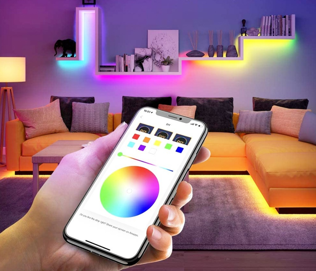person holding smart phone with color changing app to control the rainbow led lights within the room behind them