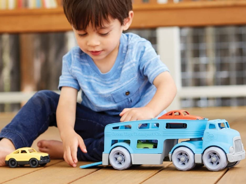 boy playing with vehicle toy set on hardwood floor