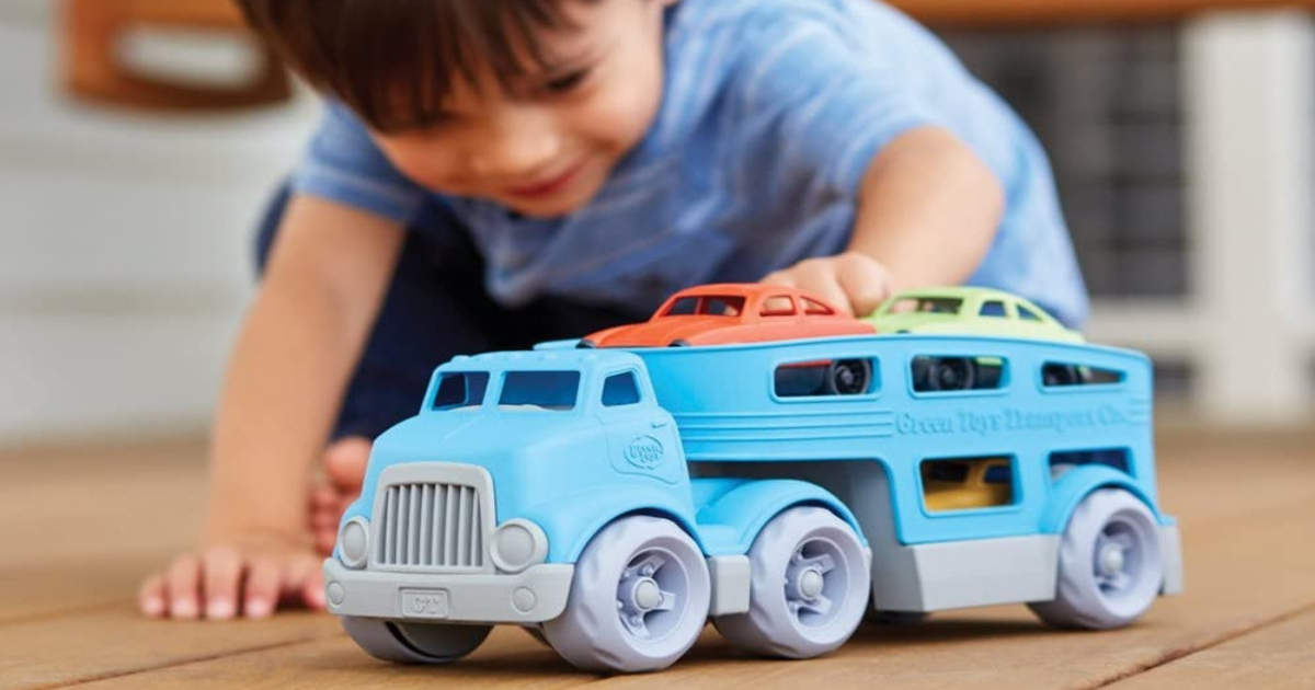 boy playing with truck car carrier on a wooden floor