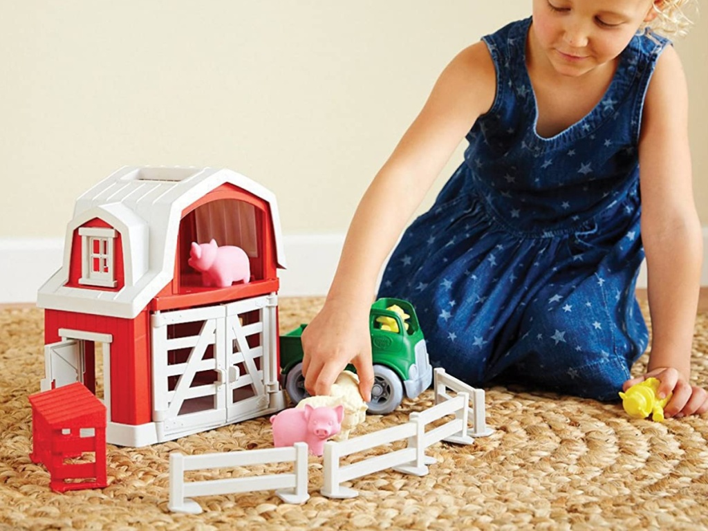 girl playing with toy farm set on carpet