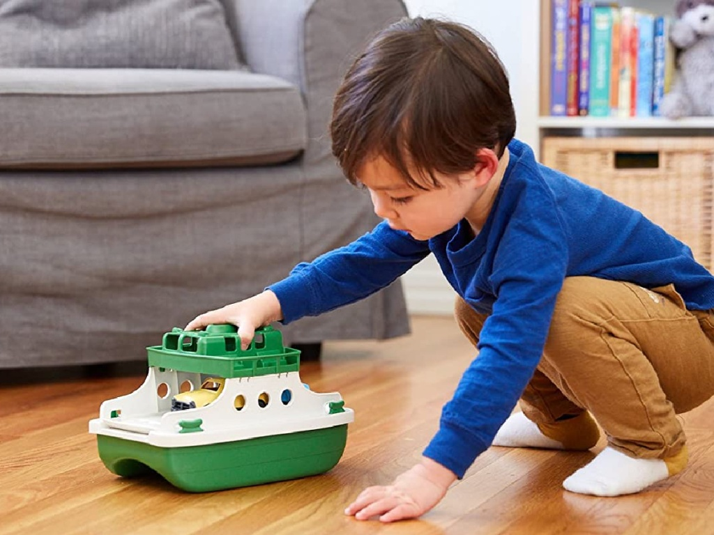 boy playing with toy ferry boat on hardwood floor