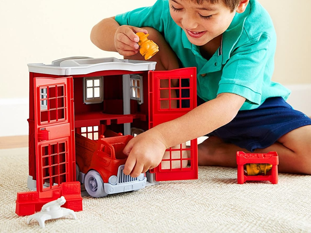 boy playing with fire station toy set on floor