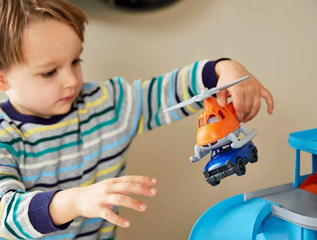 boy in striped shirt playing with orange helicopter toy that is picking up a blue car