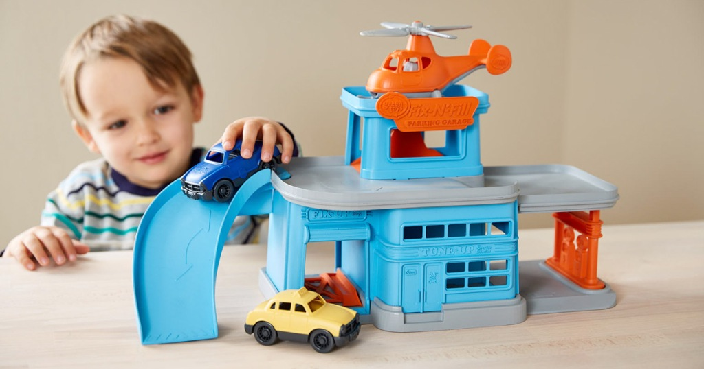 boy playing with a blue plastic parking garage toy with two cars and an orange helicopter parked on top