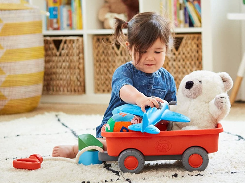 girl playing with orange wagon and other toys on carpet