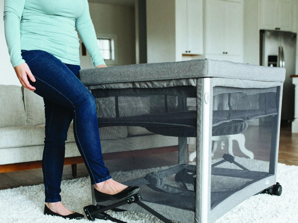 woman stepping on rocker attachment on gray bassinet