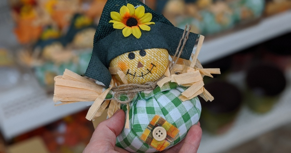 individual Harvest Inspired Scarecrow Tabletop Decor being held in hand at dollar tree