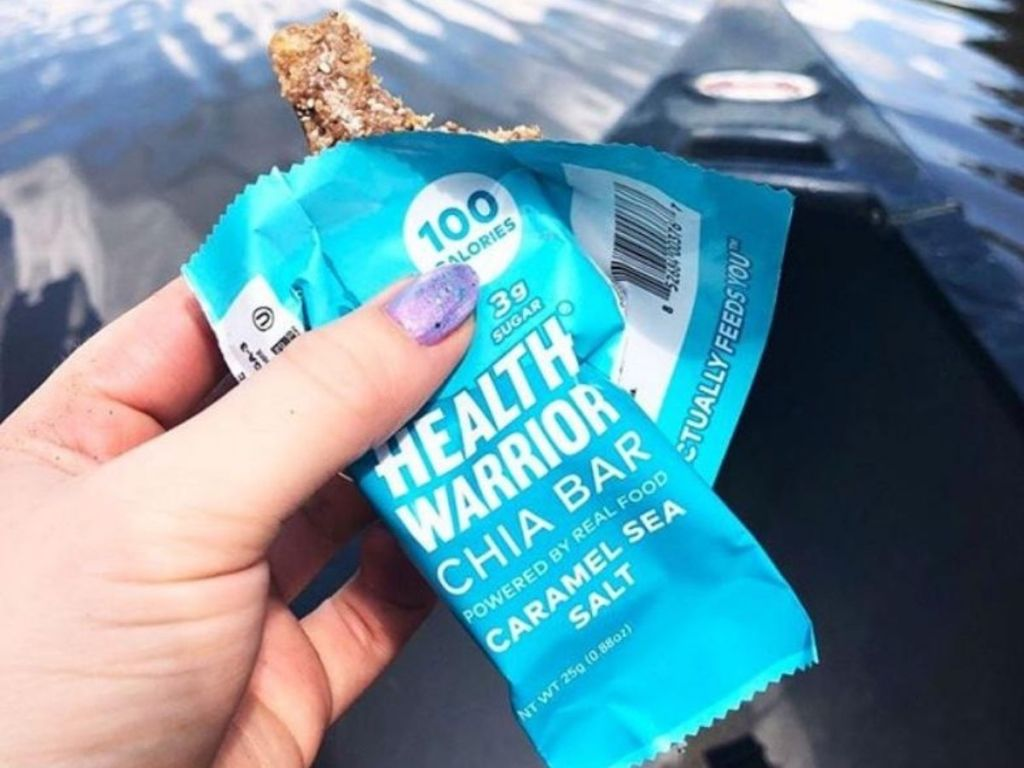 woman's hand holding a chia bar that is opened with a bite taken out