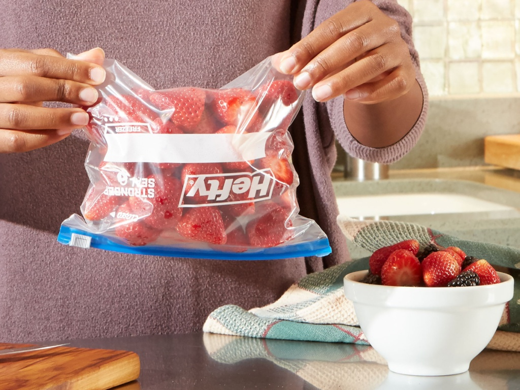 woman holding freezer bag filled with strawberries upside down in kitchen