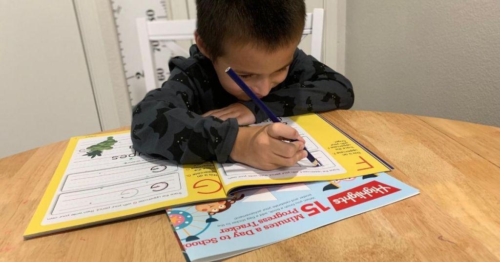 boy writing in a Highlights workbook