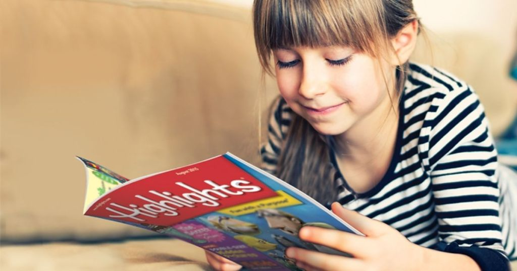 Little girl laying on stomach on couch reading magazine