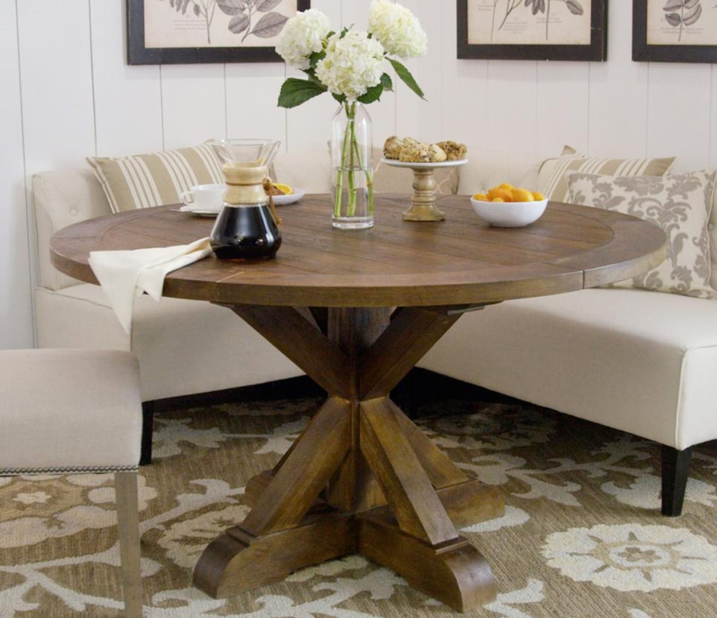 round brown farmhouse dining table with cream colored dining bench behind it