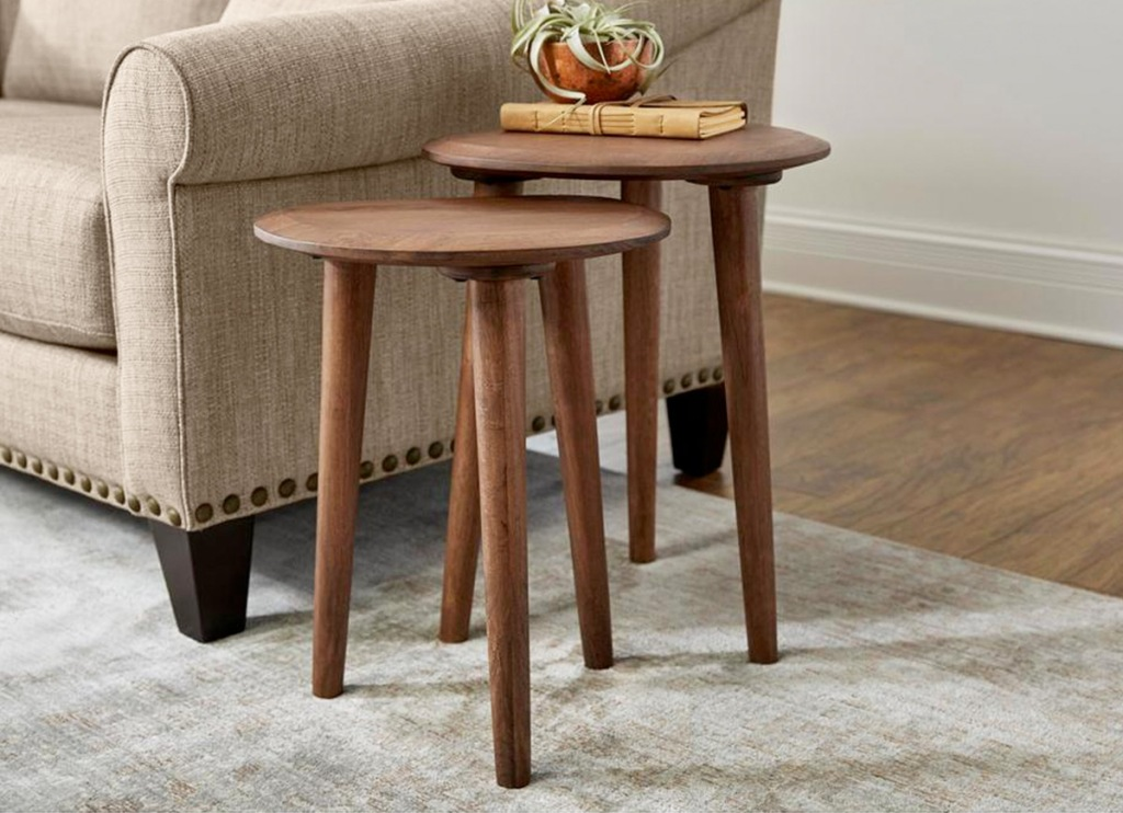 two brown accent tables nestled into one another next to beige couch