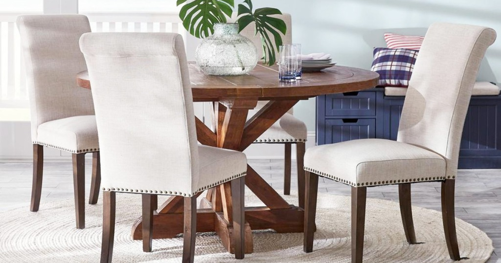 round brown farmhouse dining table with cream colored chairs around it
