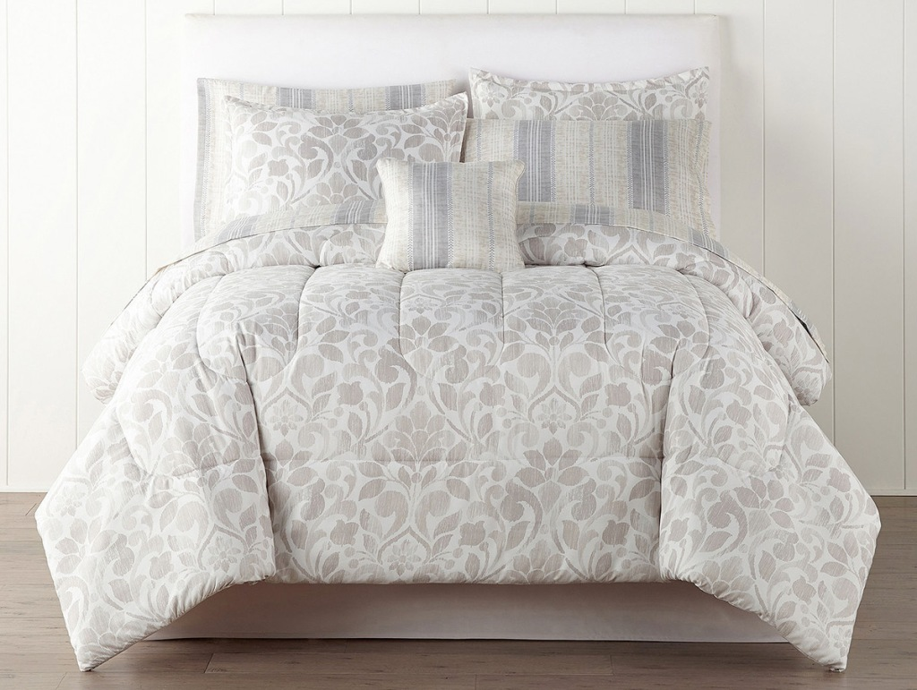 grey and white leaf printed comforter set on bed with matching pillowcases and shams