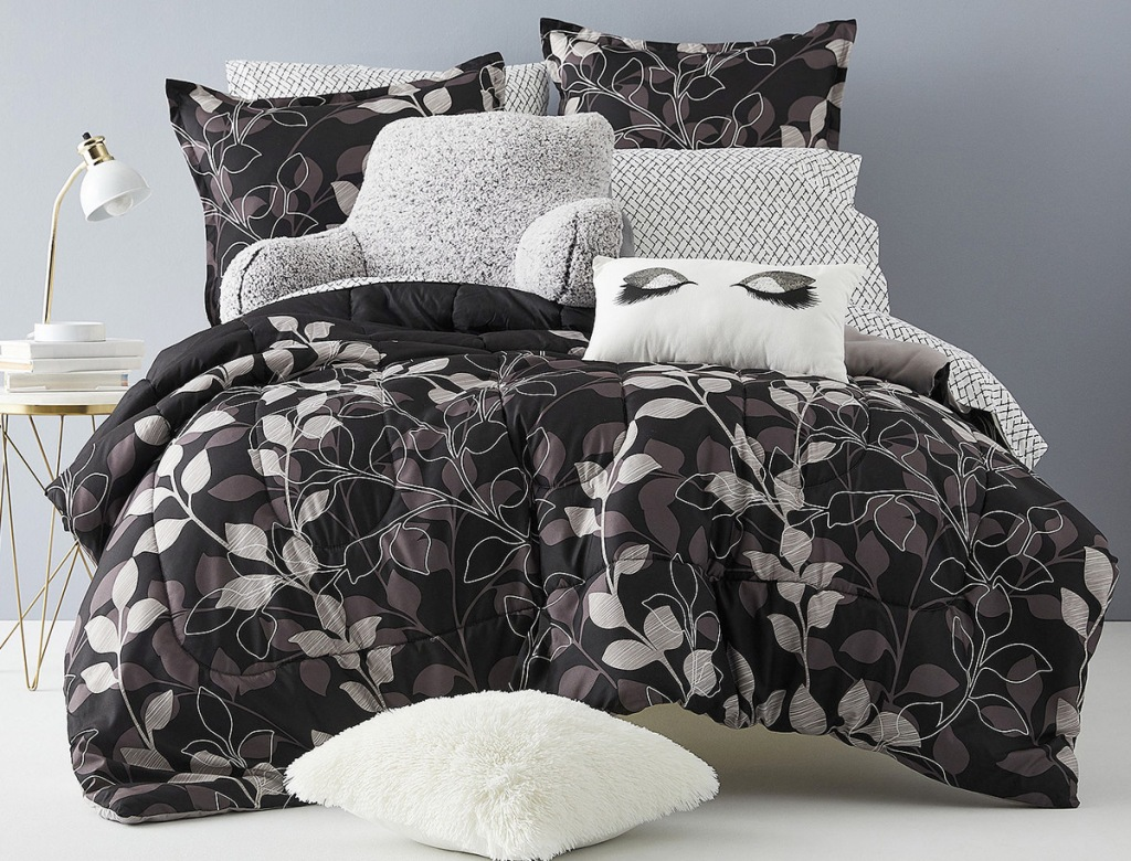 black with white and grey leaves comforter set on bed with matching pillow cases and shams