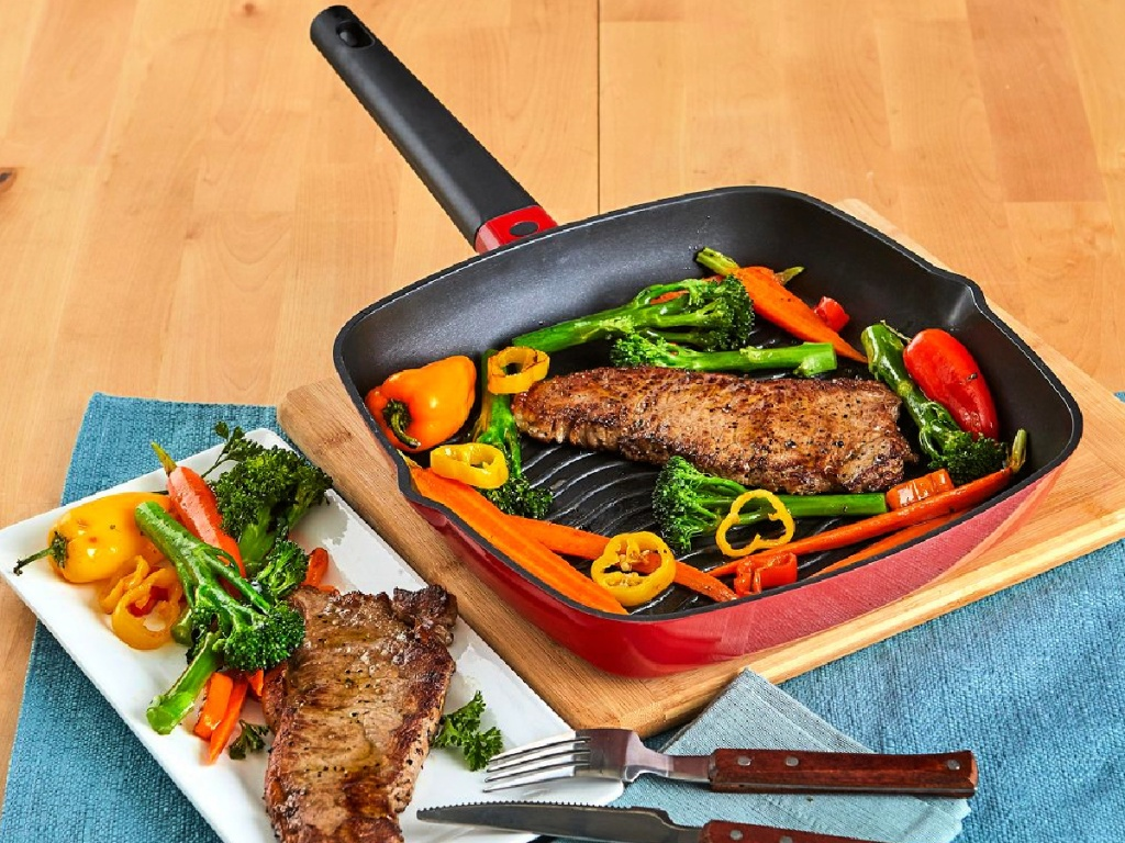 "steak and veggies being cooked on a IMUSA 11"" Red Cast Aluminum Deep Square Grill Pan"