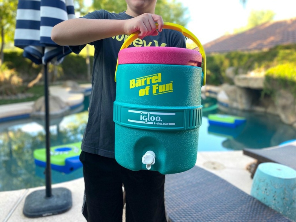 boy holding a igloo cooler by a pool