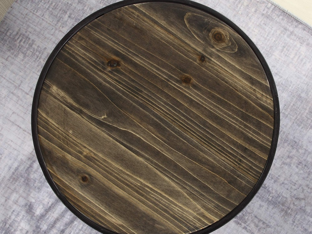Round wooden table top on industrial style end table