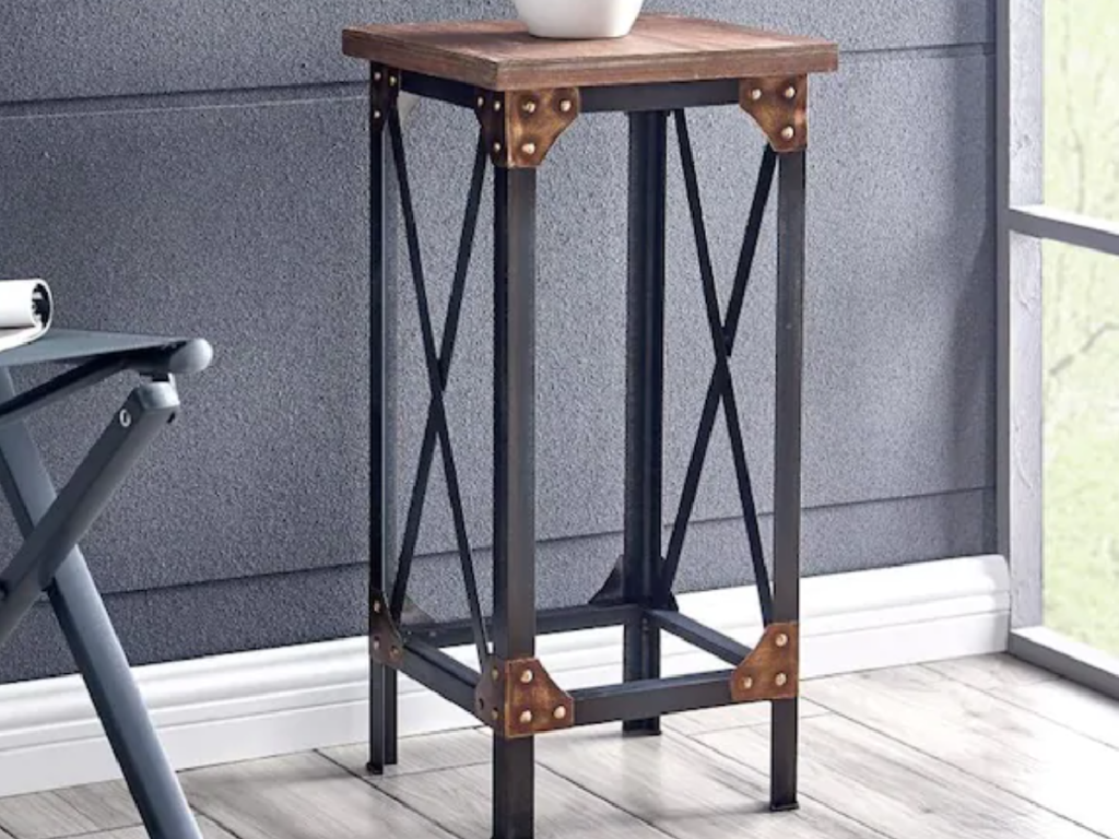 industrial style tall end table next to a window and chairs