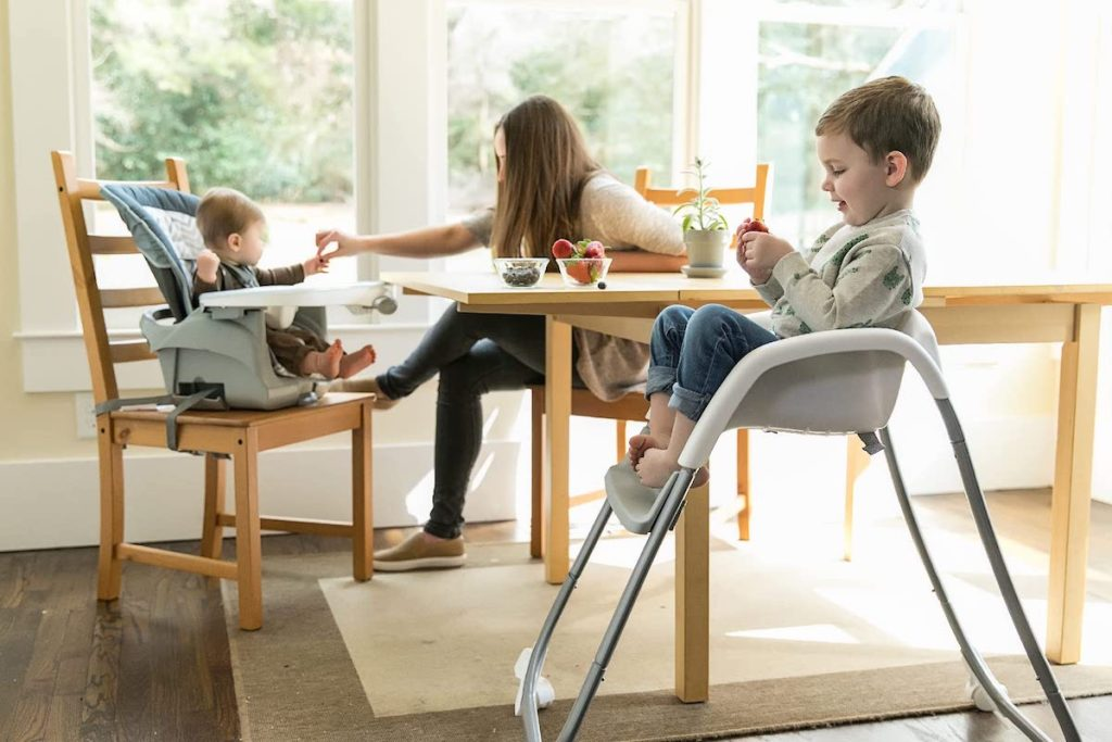 toddler sitting in Infantino toddler Chair and baby sitting in High chair
