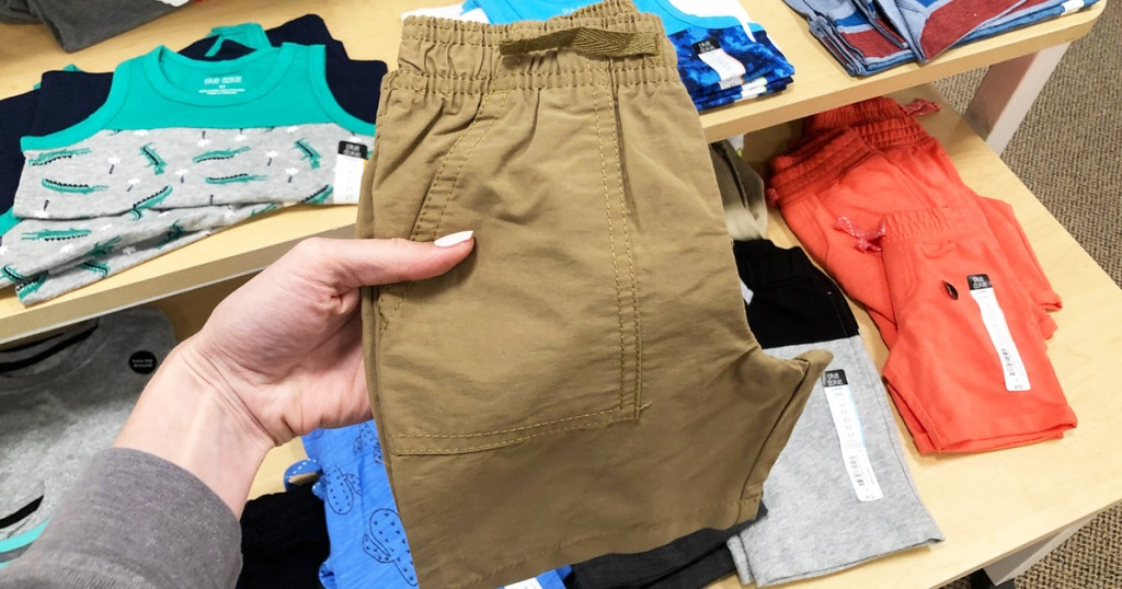 woman holding up a brown pair of toddler boys shorts in front of display of other kids apparel items