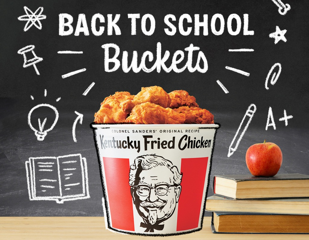 bucket of KFC fried chicken with stack of books, apple, and blackboard with school themed doodles behind it