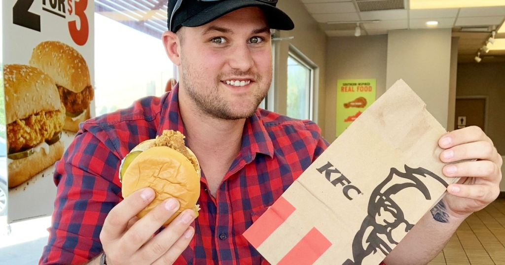 man in red and black plaid shirt holding up a brown KFC bag and fried chicken sandwich