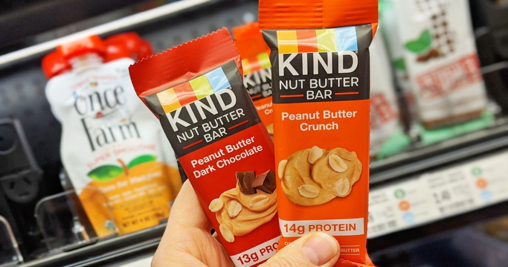 person holding up red and orange KIND nut butter bars