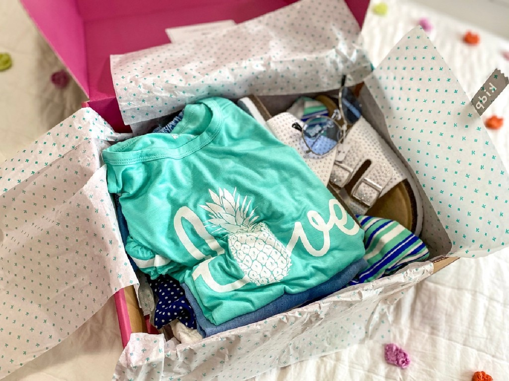 shipping box filled with girls clothing, shoes, and accessories on bed