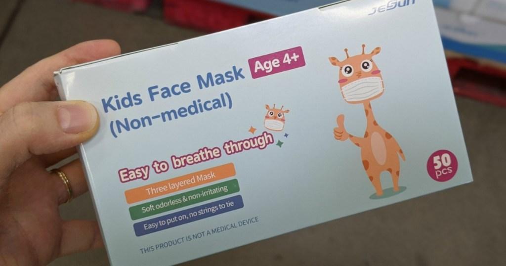 Man's hand holding a box of kids face masks