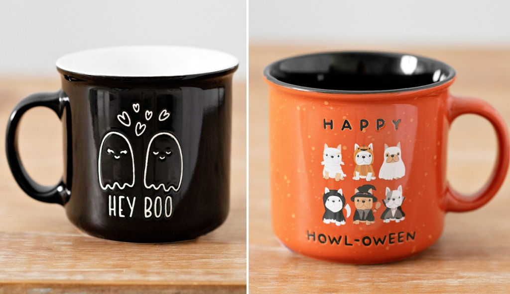 "black ghost themed coffee mug that says ""hey boo"" and orange coffee mug with dogs in halloween costumes"