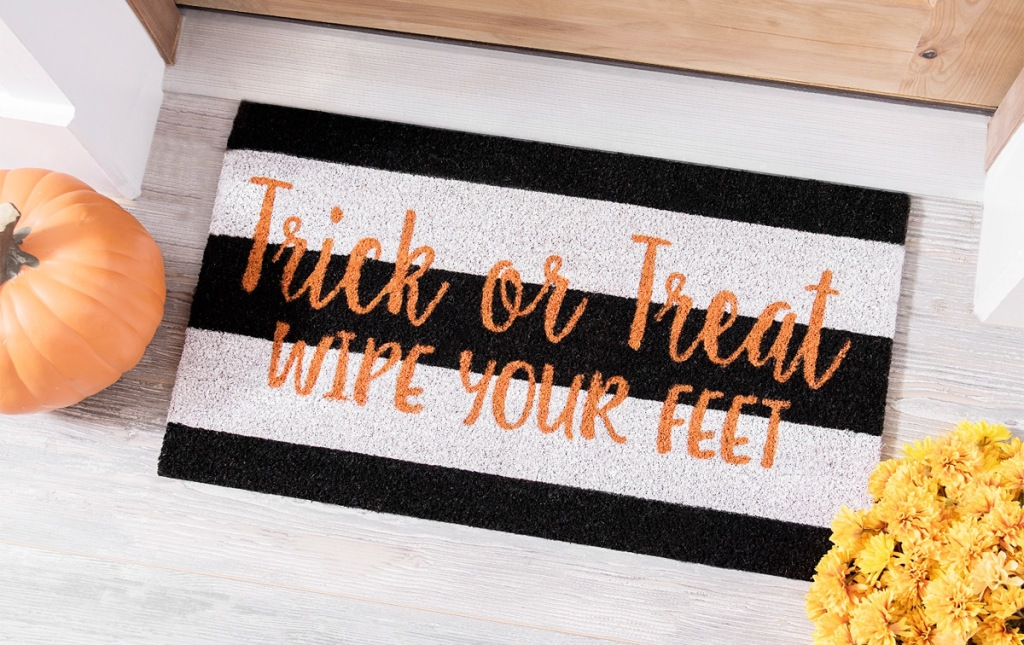 black and white striped doormat that says trick or treat wipe your feet in orange