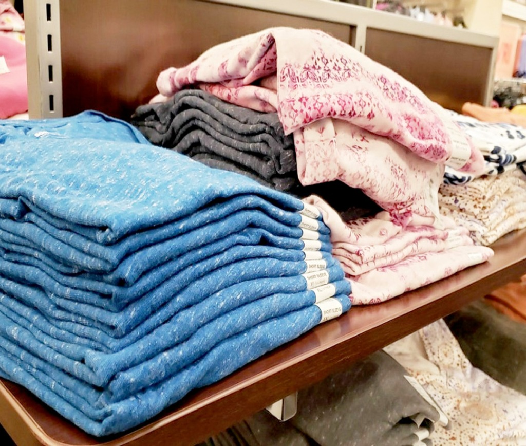 folded women's tees in various colors and prints on a Kohl's store display shelf