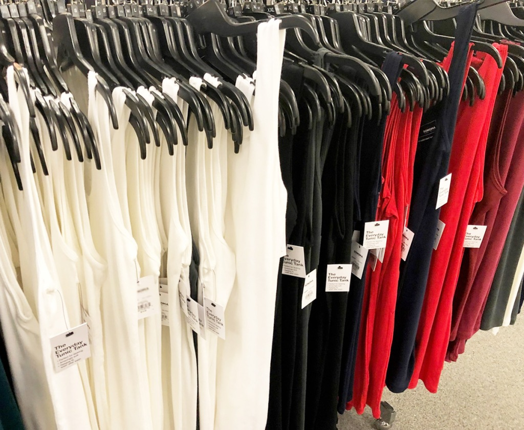 women's basic tank tops in white, black, and red colors on hangers on store display rack