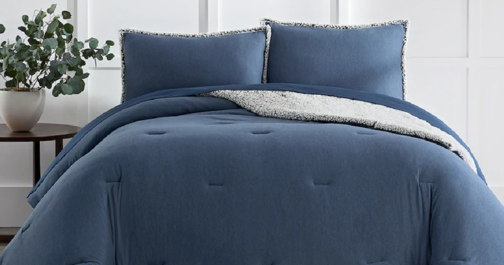 Blue Koolaburra by UGG bedding and shams on a queen size bed next to a nightstand