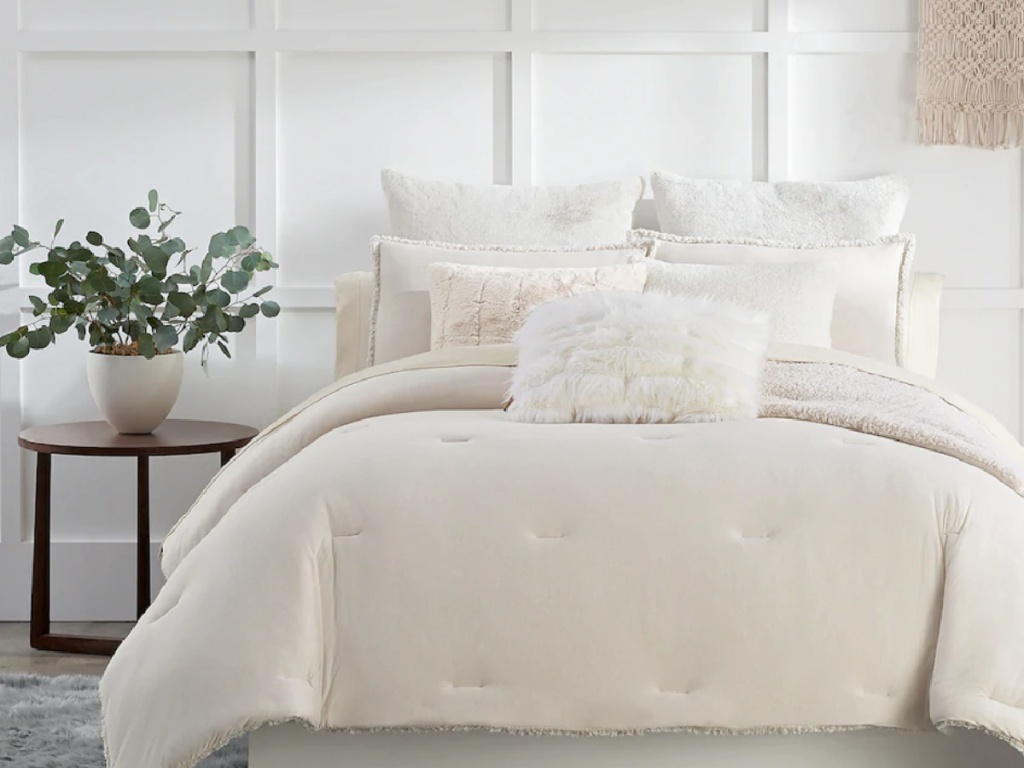 cream colored cozy bedding and shams on a queen size bed next to a side table with a plant
