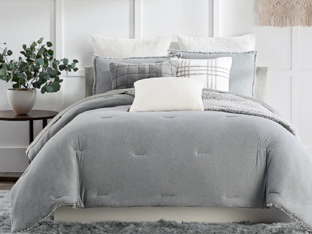 light grey cozy bedding and shams on a queen size bed next to a side table with a plant