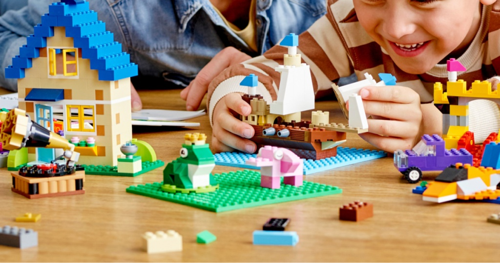 child and adult plating with LEGO set on table