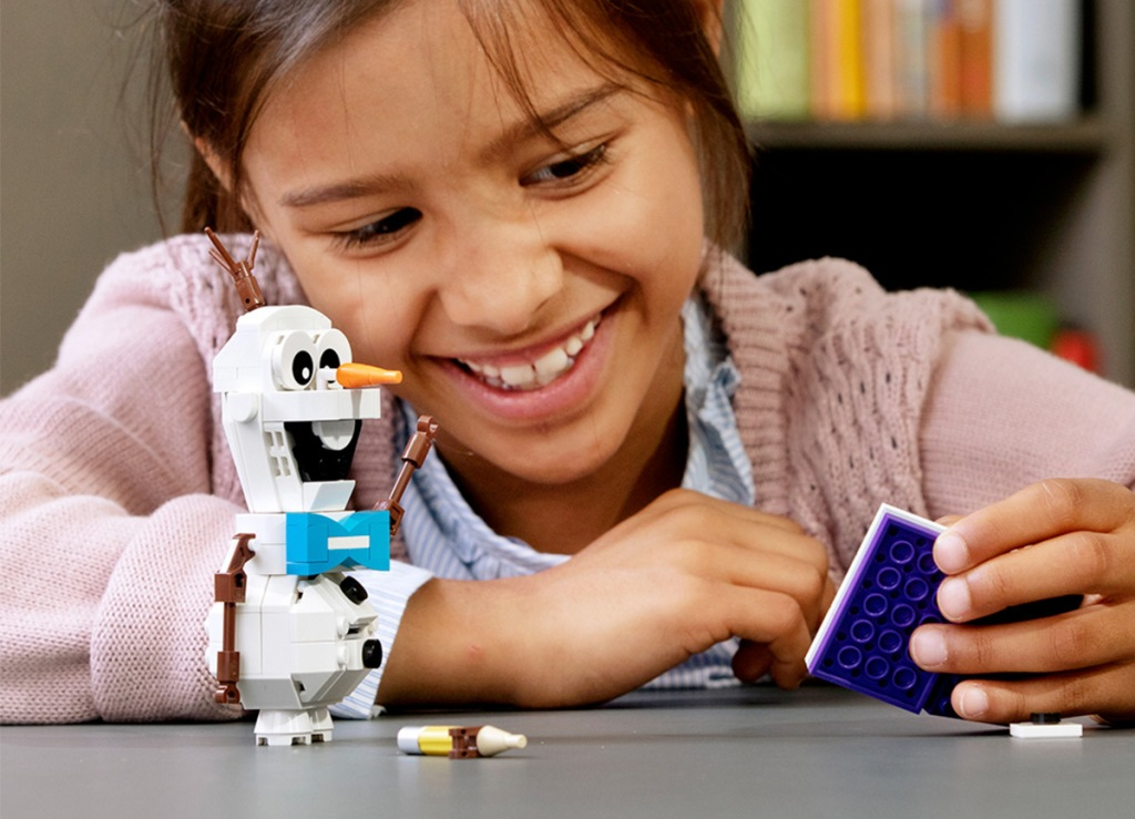 girl playing with a LEGO figure of Olaf the snowman from Frozen 2